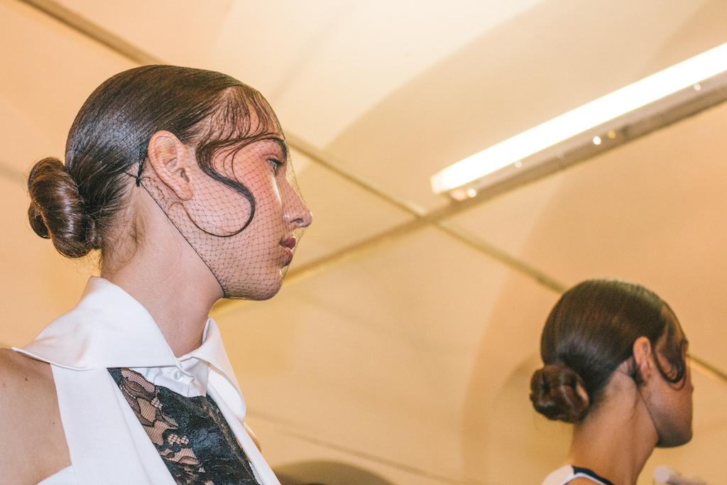 """All'ombra dei Chiostri di San Barnaba, a Milano, ha sfilato una Lady Macbeth contemporanea, con un hairstyle """"sleek and chic"""" firmato Toni Pellegrino. Sabato 24 Febbraio è stato scritto un nuovo capitolo della collaborazione tra Mario Dice, designer pugliese sempre più in ascesa, e l'hairstylist siciliano. Hairstyle raffinato firmato Toni Pellegrino per Mario Dice In occasione della recente Milano Fashion Week, Dice ha affidato all'ArTeam di Toni Pellegrino la realizzazione delle acconciature per la presentazione della sua collezione F/W 2018/2019. L'hairstyle scelto per la sfilata: un raffinatissimo chignon basso, delle onde effetto bagnato sulla fronte, e una retina dal sapore"""
