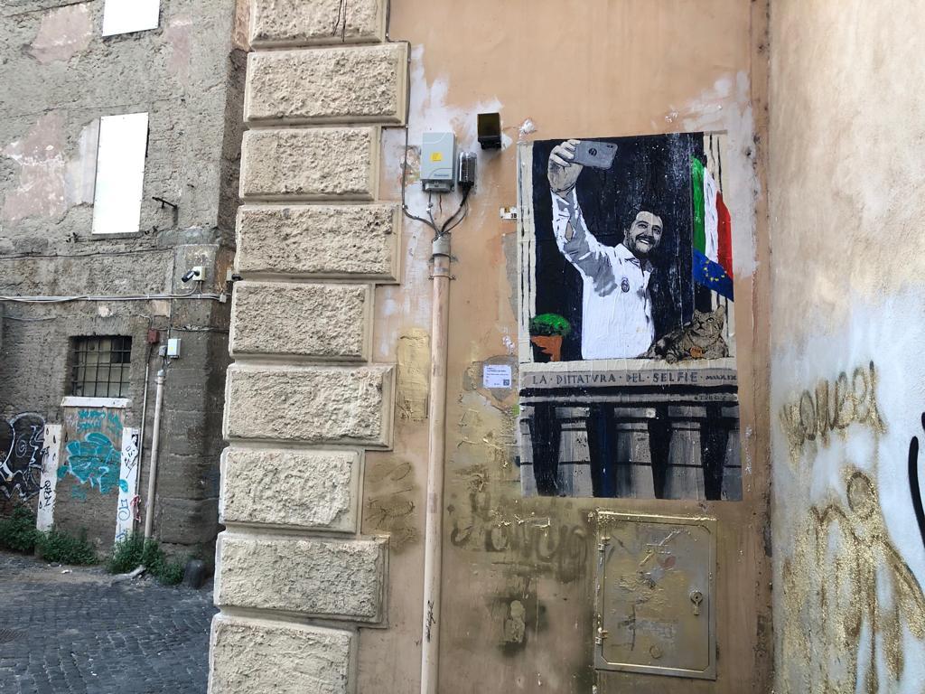 """Nuova azione di Tvboy nella capitale. La scorsa notte lo street artist di origini siciliane è tornato a Roma con una nuova provocazione che ha per protagonista il ministro Matteo Salvini. L'opera si intitola """"La Dittatura del Selfie"""" ed è stata affissa a via Dei Polacchi, zona Piazza Venezia."""